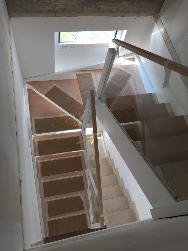 escalera de linea moderna con barandilla de cristal. newak.es
